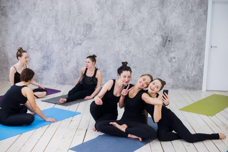 做selfie的三个少妇在锻炼以后在瑜伽类 免版税图库摄影