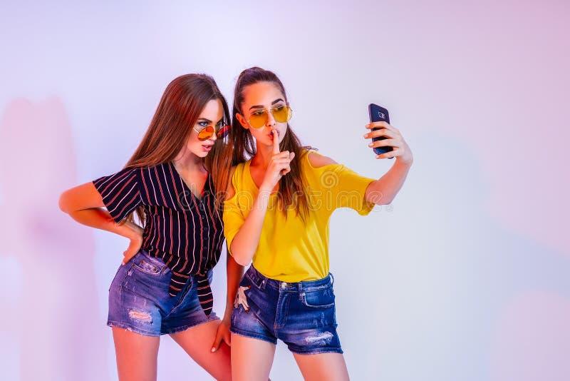 做selfie的十几岁的女孩在智能手机 库存图片