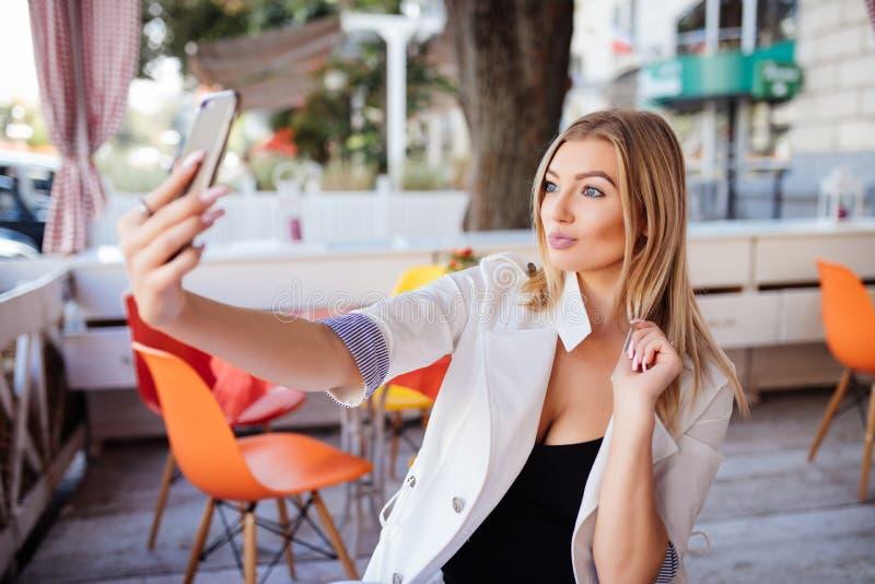 做selfie的华美的微笑的妇女,当食用一杯咖啡时 库存照片