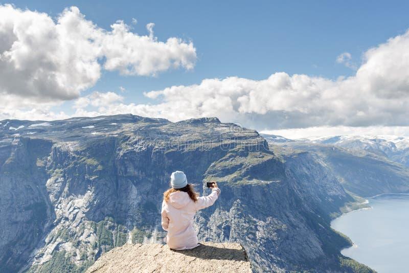 做selfie的妇女远足者使用巧妙的电话,当放松在cli时 图库摄影