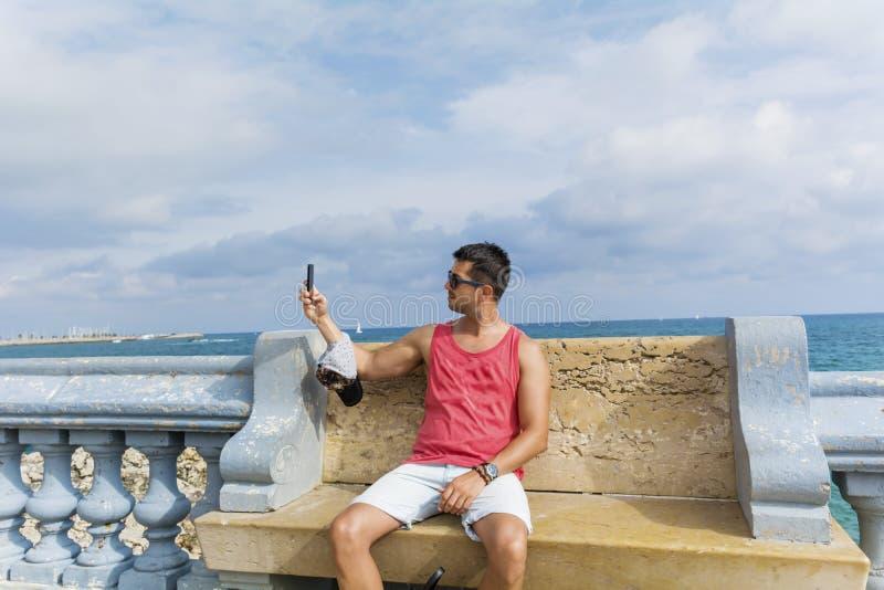做selfie的年轻人在一条长凳有海视图 库存照片