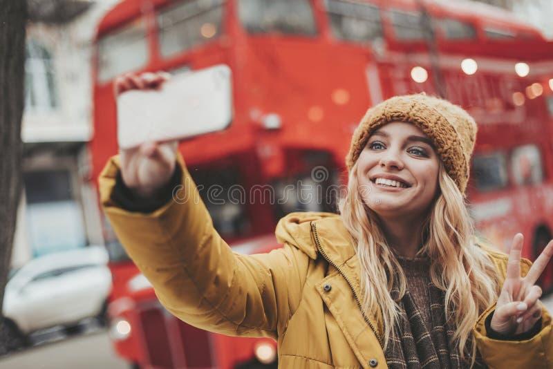 做selfie的年轻愉快的妇女在街道 库存照片