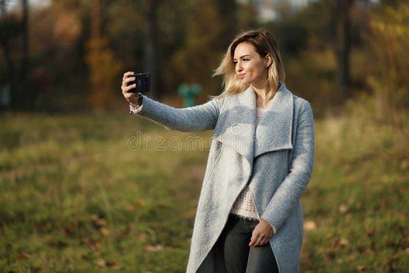 做selfie的年轻美丽的女孩在公园 秋天背景特写镜头上色常春藤叶子橙红 免版税库存图片
