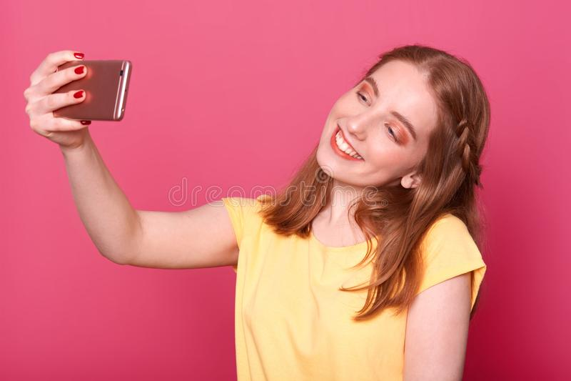 做selfie的年轻美丽的时髦的妇女接近的画象,使用她自己的智能手机,微笑在照相机,穿戴了偶然 库存照片