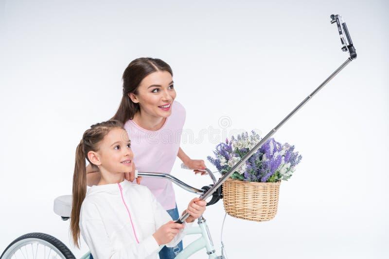 做selfie的微笑的母亲和女儿在白色 免版税图库摄影
