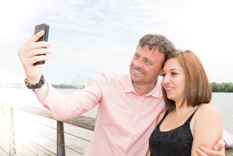 做selfie的快乐的年轻爱恋的夫妇在照相机,当站立户外时 库存图片