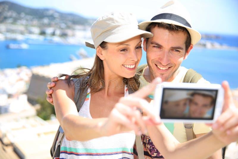 做selfie的旅行家夫妇由海 免版税库存照片