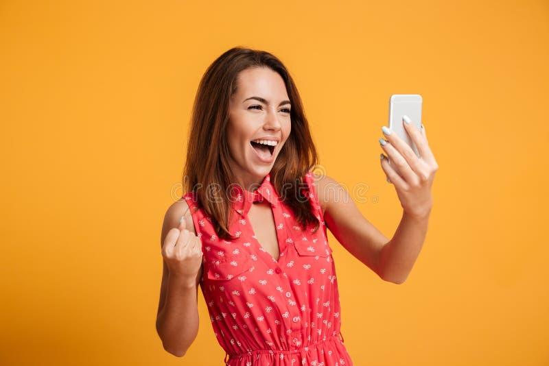 做selfie的礼服的愉快的叫喊的深色的妇女在智能手机 免版税库存图片