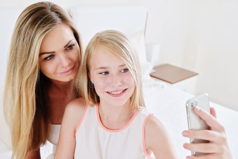 做selfie的美丽的成熟母亲和她的女儿画象使用巧妙的电话和微笑 免版税库存图片