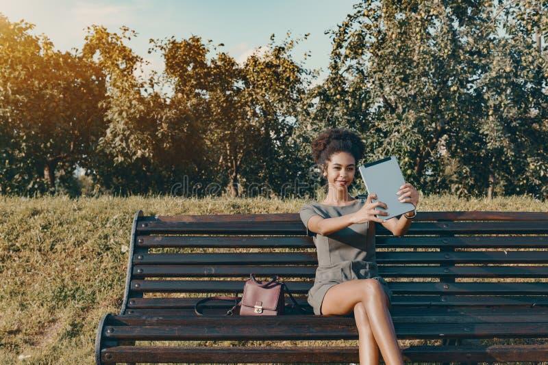 做selfie的蓬松卷发ameican女孩在公园 免版税图库摄影