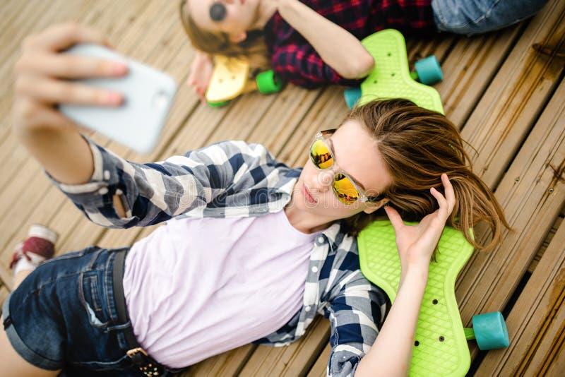 做selfie的行家成套装备的年轻时髦的都市女孩,当说谎与在木码头时 免版税库存照片