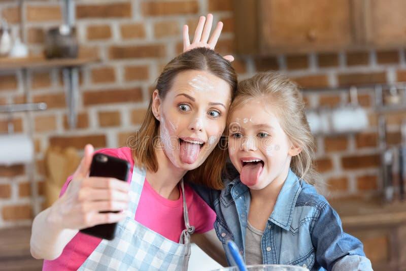 做selfie的鬼脸母亲和女儿,当在家时烹调 免版税库存照片