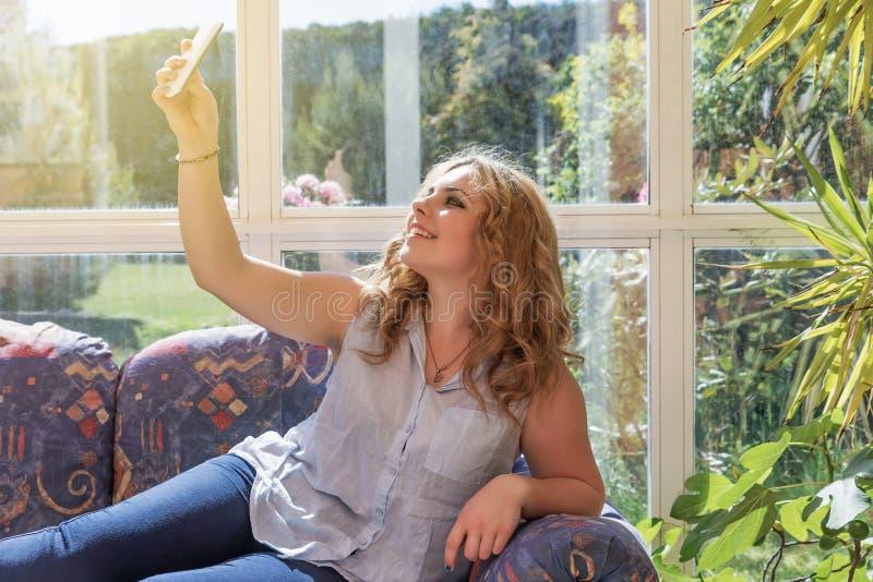 做selfie的年轻俏丽的女孩说谎在沙发 库存照片