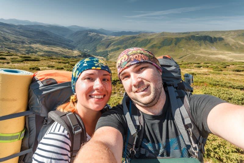 做selfie雪手段山的年轻夫妇 免版税库存照片