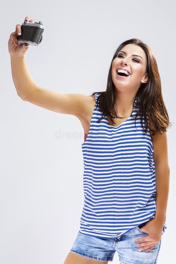 做Selfie -与古板的胶卷相机的照片的运动衫的白种人深色的女孩 免版税库存图片
