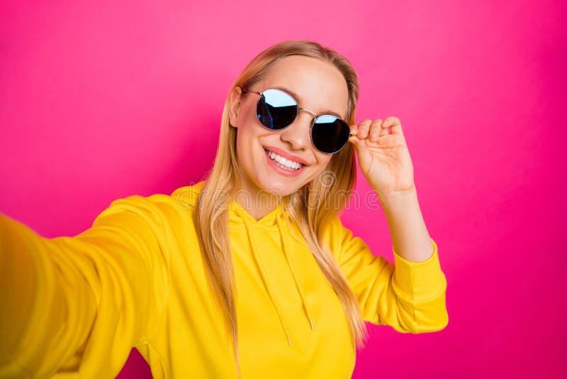 做selfies的凉快的夫人特写镜头照片佩带太阳specs黄色套头衫被隔绝的桃红色背景 免版税图库摄影