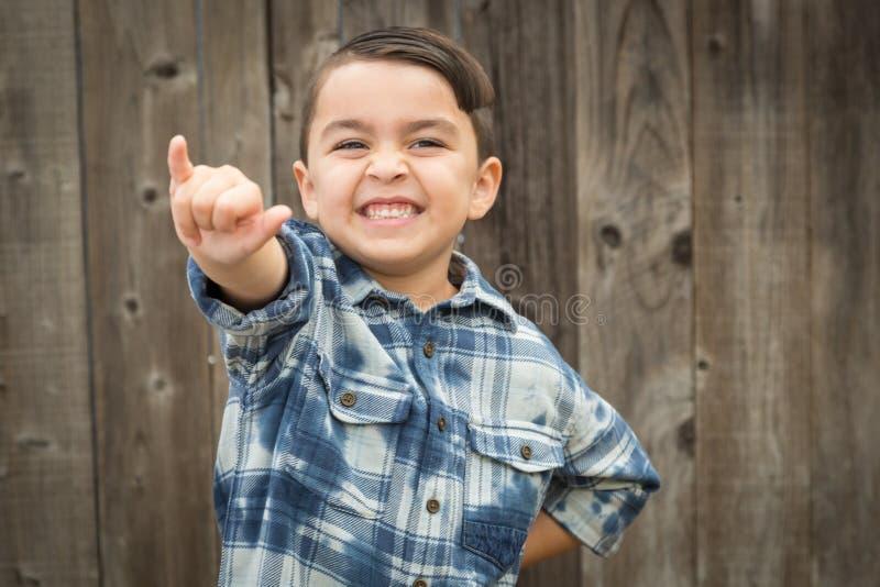 做Shaka手势的逗人喜爱的年轻混合的族种男孩 库存照片