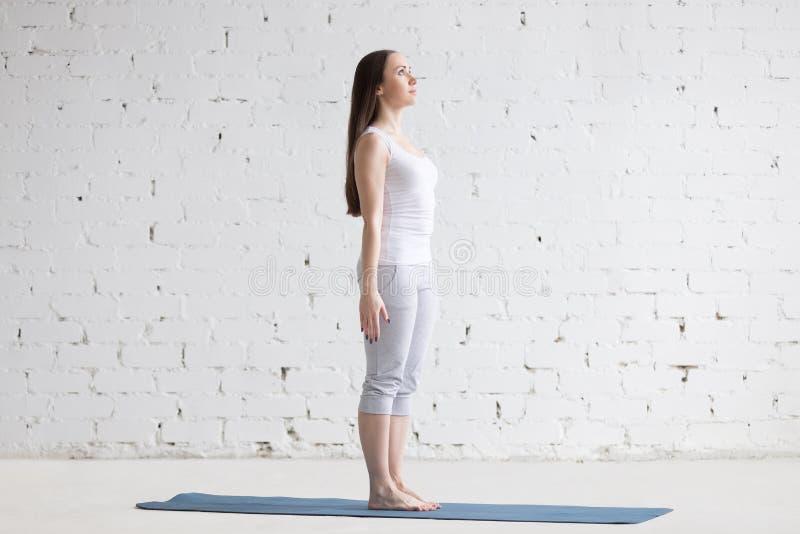 做Tadasana姿势的美丽的运动的少妇在白色顶楼 免版税库存图片