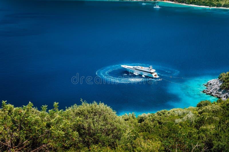 停住在一个平静的海湾的豪华白色游艇帆船在深大海水中,在希腊语附近美丽如画的岸  免版税库存照片