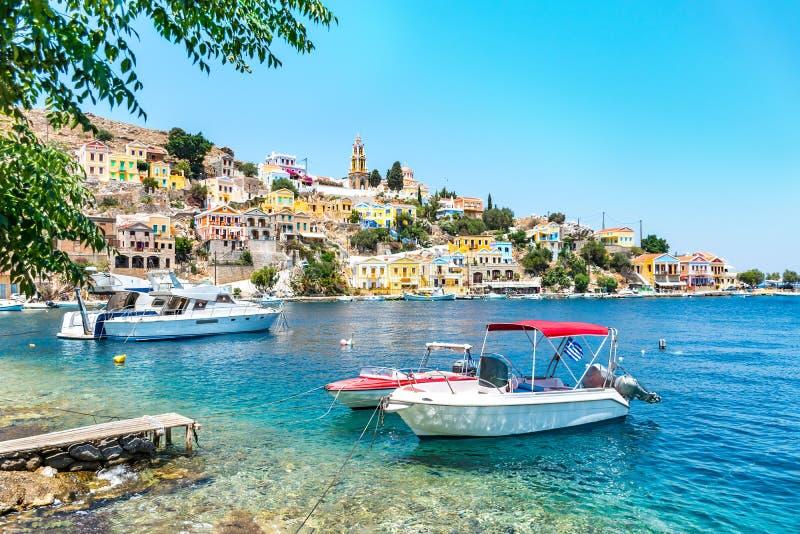 停住的小船和五颜六色的新古典主义的房子锡米岛锡米岛海岛,希腊海湾的  图库摄影