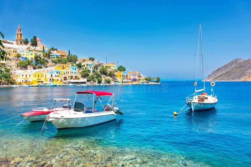 停住的小船和五颜六色的新古典主义的房子锡米岛锡米岛海岛,希腊海湾的  免版税库存图片