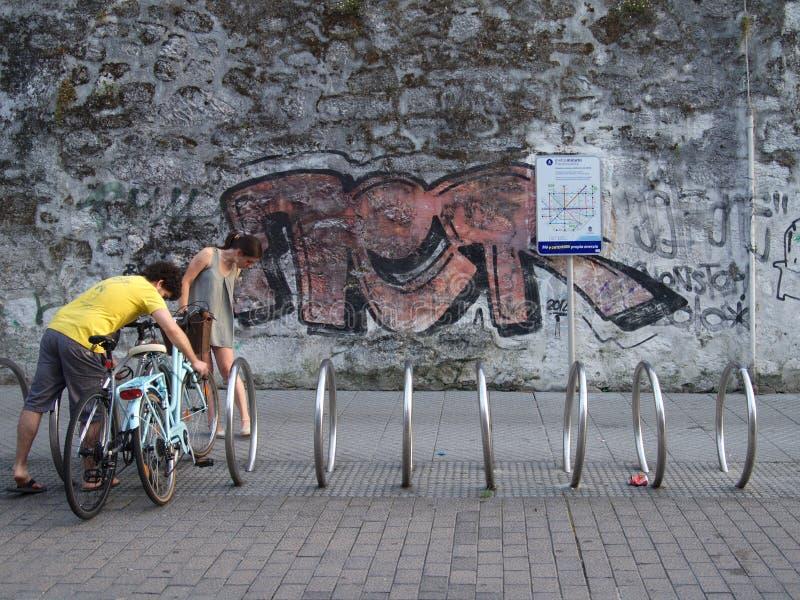 停放他们的自行车的年轻夫妇在镇里在街道画墙壁前面的一个自行车行李架 免版税库存照片