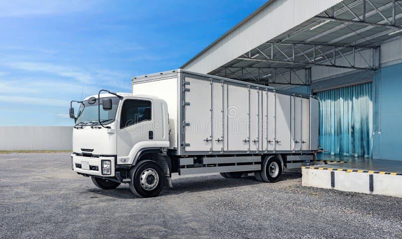 停放在商品装货的工厂仓库的运输卡车 免版税库存图片