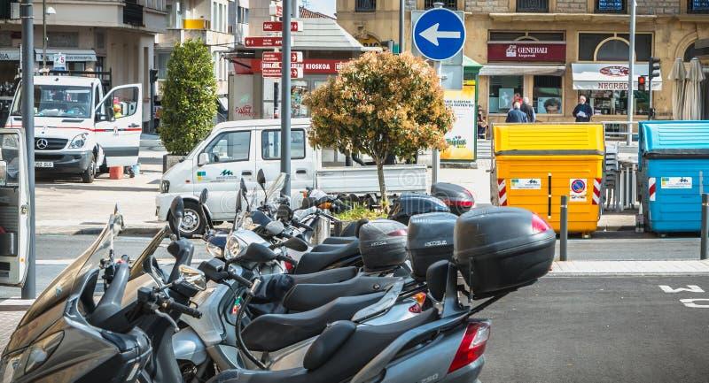 停放在城镇厅附近的摩托车和出租汽车在伊伦,西班牙 免版税库存图片