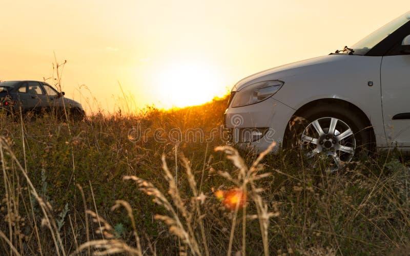 停放在草甸的两现代汽车侧视图在日落 免版税库存图片
