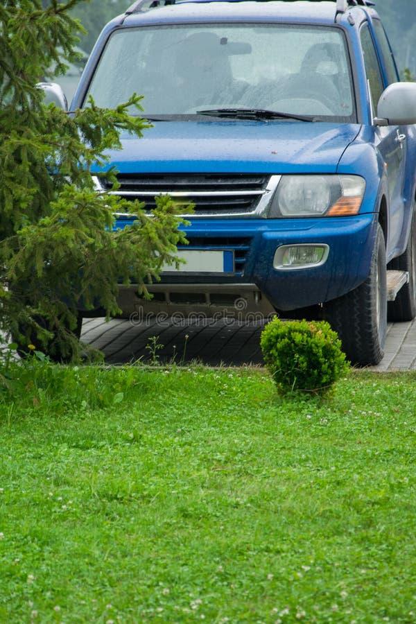 停放的公路车辆的正面图在绿色草坪前面的在fr 免版税库存照片
