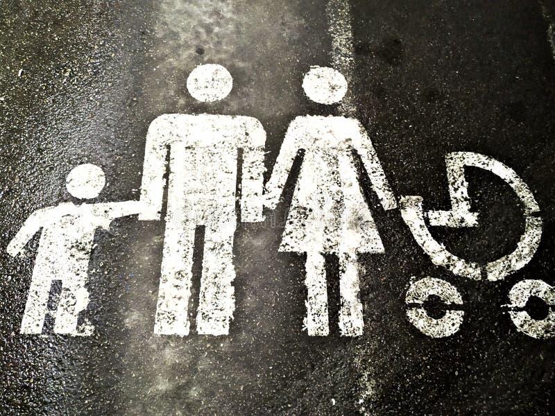 停放的汽车的家庭标志有孩子的 绘与在灰色沥青的白色油漆 免版税库存图片