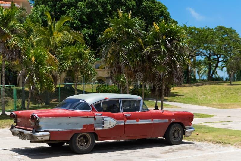 停放的红色葡萄酒汽车在海滩附近的哈瓦那古巴 库存图片