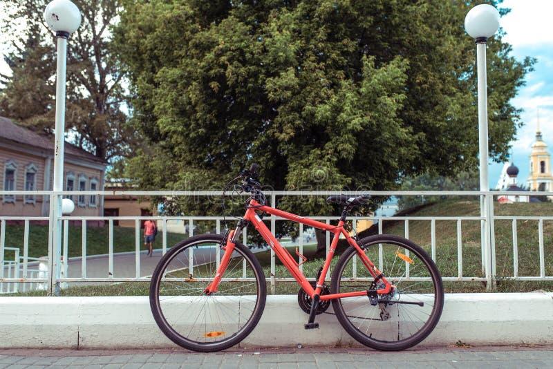 停放的自行车在城市、红色黑方向盘和椅子的夏天与轮子 背景树与灯的篱芭柱子 免版税库存照片