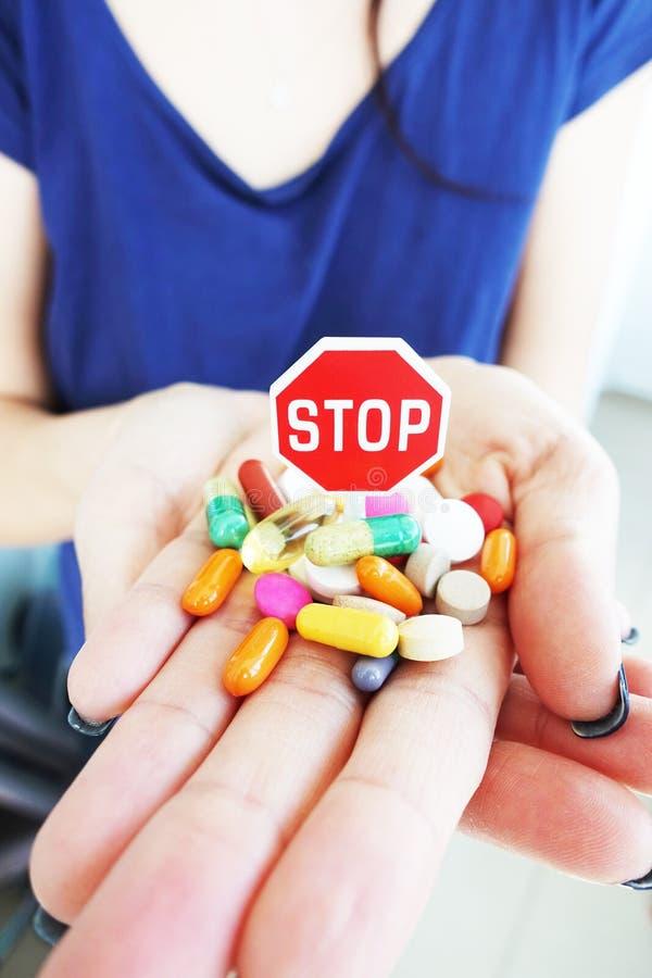 停止使用与微型中止路标和五颜六色的药片的药物或抗抑郁剂概念在妇女手 免版税库存照片