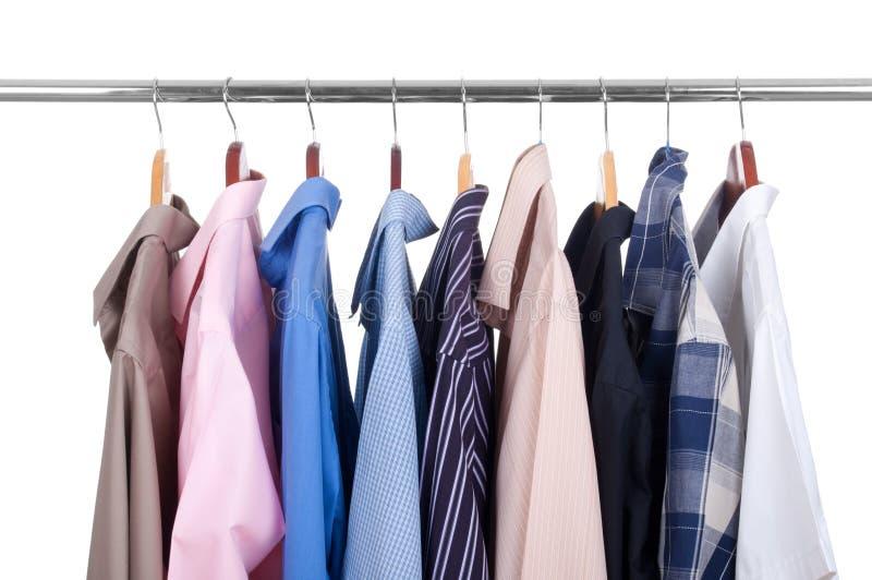 停止在挂衣架的五颜六色的行衬衣行  库存图片