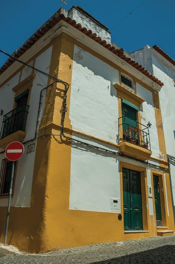 停止在有大阳台的前面五颜六色的房子里路标 图库摄影