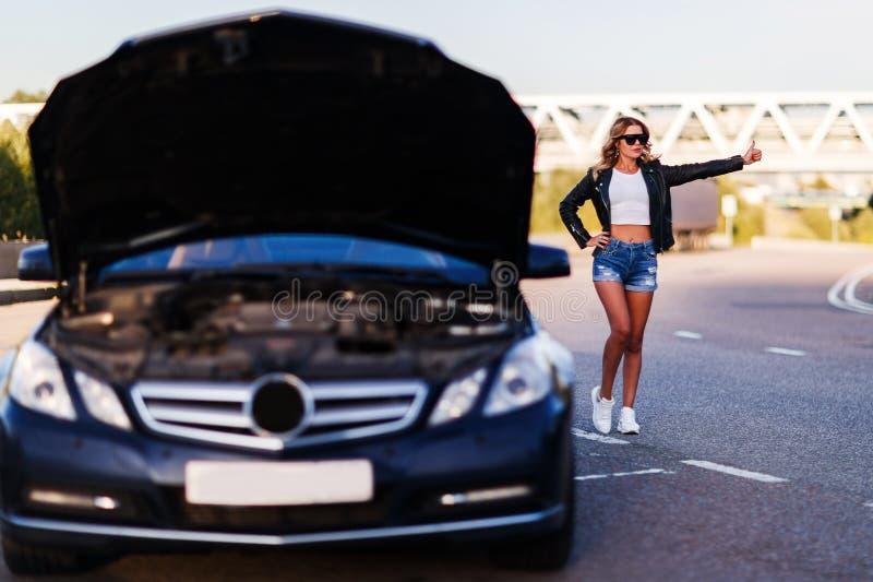 停止在街道上的年轻白肤金发的妇女的图象汽车 免版税库存照片