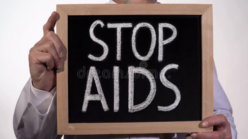 停止在黑板在医生手上,疾病预防的艾滋病警告词组 图库摄影