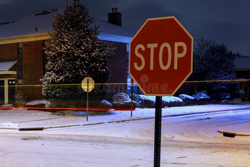 停止签到有光亮的街灯的冬天降雪的夜被盖的冬天路在乡区 免版税图库摄影