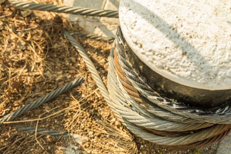 停泊在水泥块固定的一部分的港设备粗糙的扭转的绳索铁生锈的被风化的特写镜头 免版税库存图片