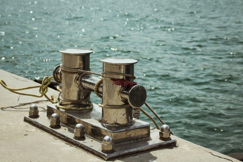 停泊系船柱,交错与停泊绳索在海湾的口岸 图库摄影