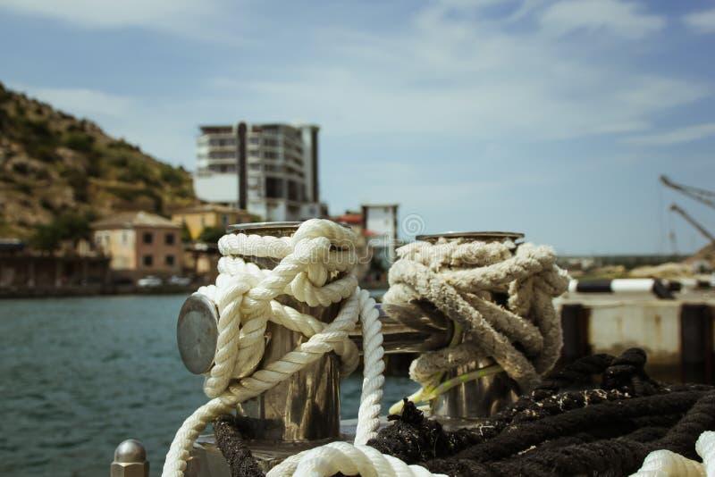 停泊系船柱,交错与停泊绳索在海湾的口岸 免版税库存照片