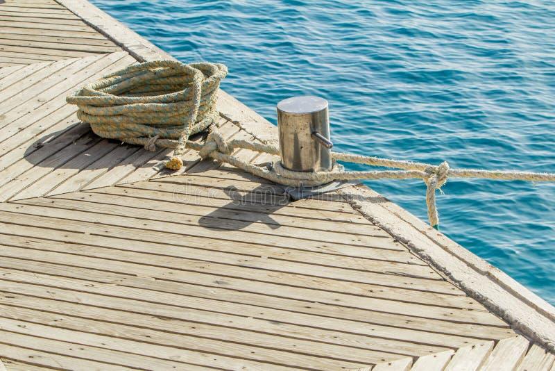 停泊绳索和系船柱在海水和游艇背景 库存照片