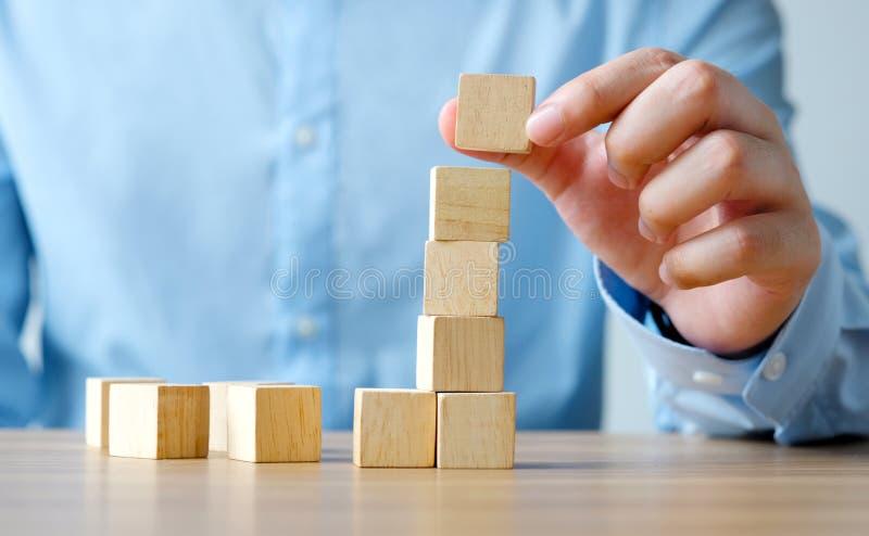 停滞在木桌,企业概念背景上的手空白的木立方体,假装,模板 免版税库存照片