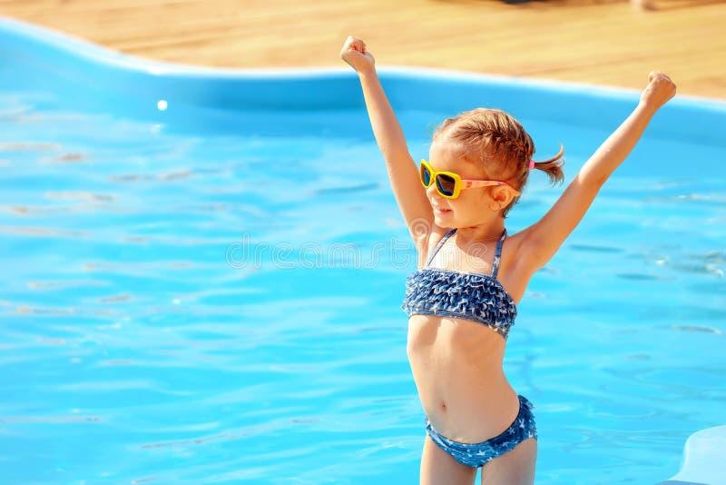 停滞手的小逗人喜爱的女孩在游泳池附近 免版税库存照片