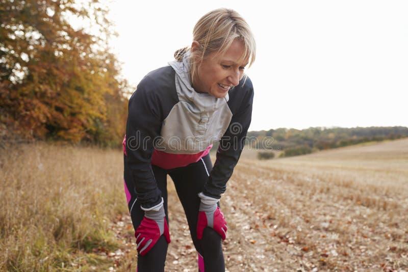 停留为呼吸的成熟母赛跑者在锻炼期间在森林 免版税库存图片