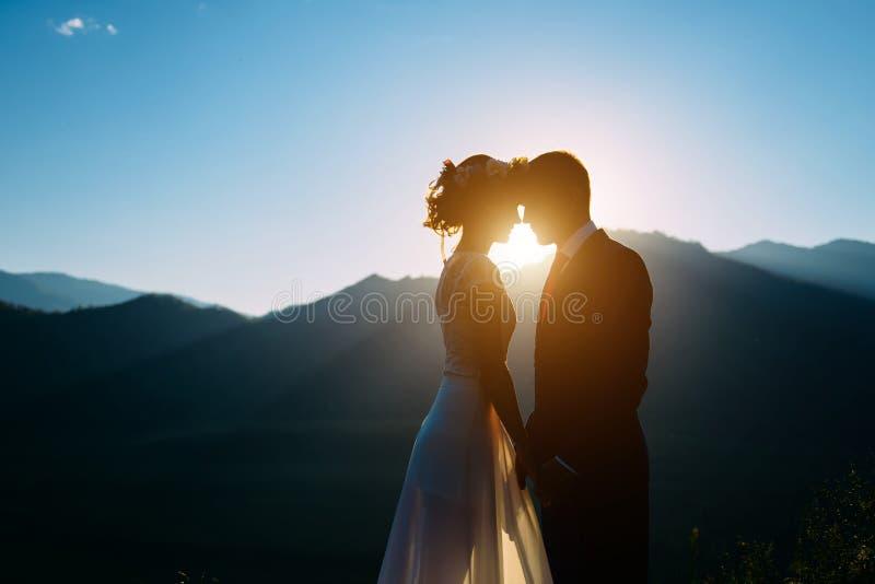 停留和亲吻在与山的美好的风景的愉快的婚姻的夫妇 图库摄影
