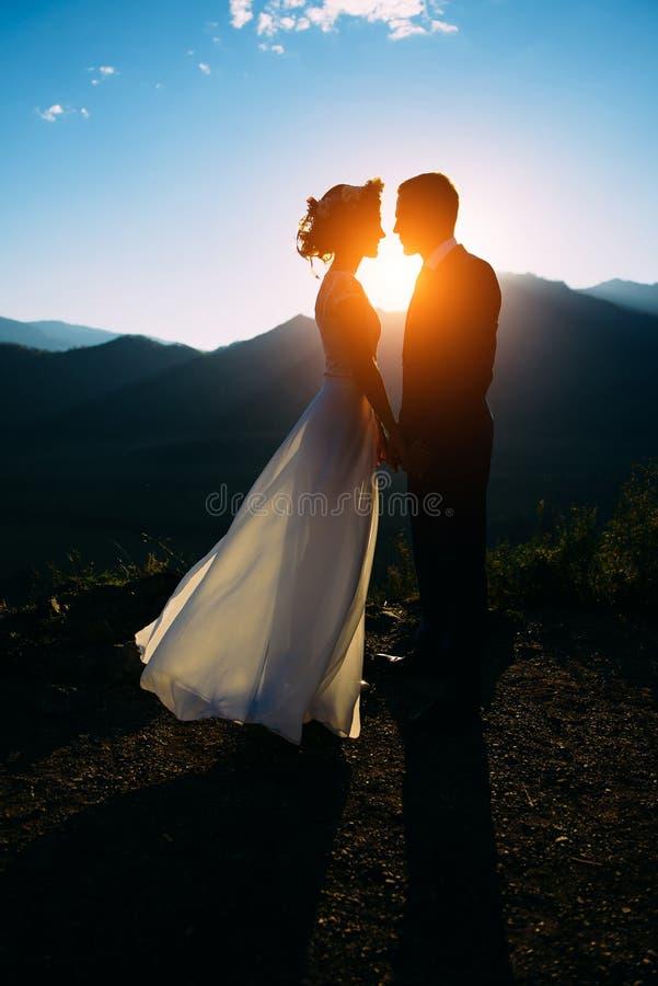 停留在与山的美好的风景的愉快的婚姻的夫妇 免版税库存图片