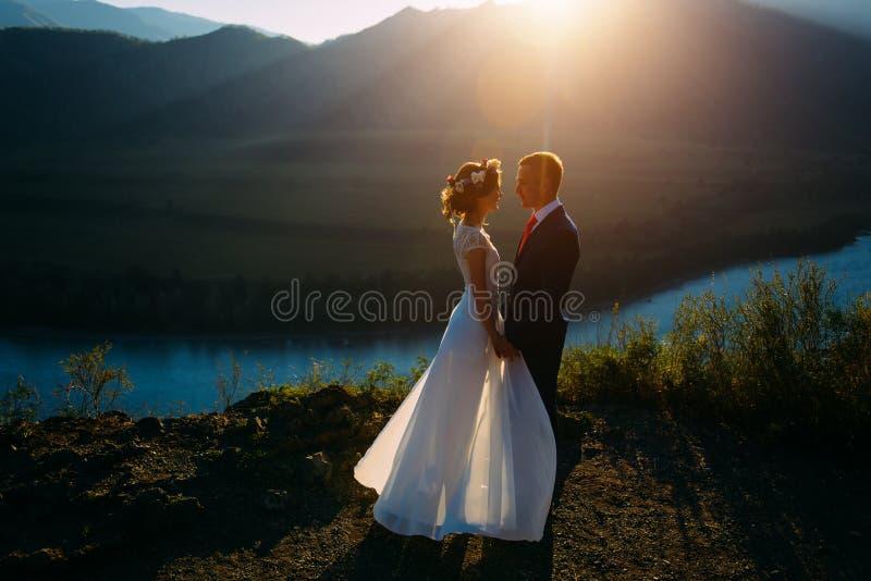 停留在与山的美好的风景的愉快的婚姻的夫妇 免版税库存照片