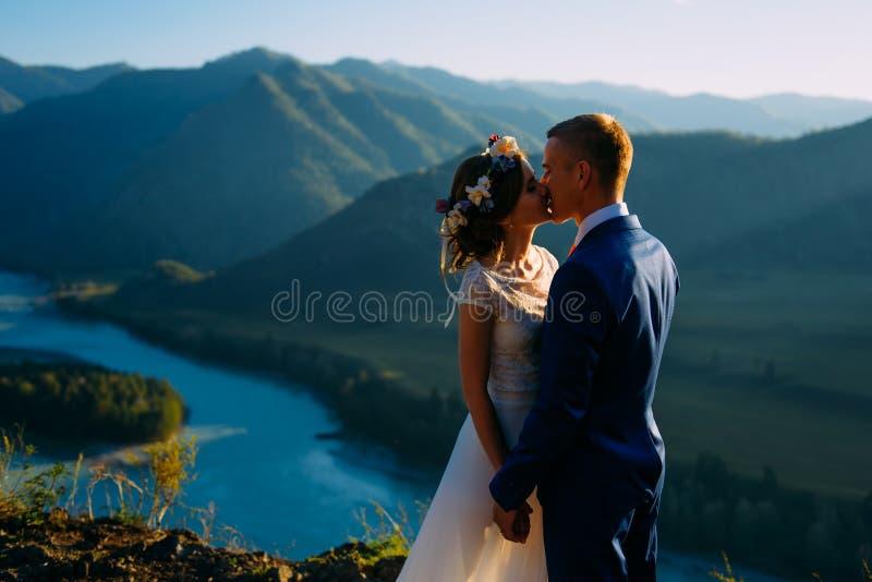 停留在与山的美好的风景的愉快的婚姻的夫妇 免版税图库摄影